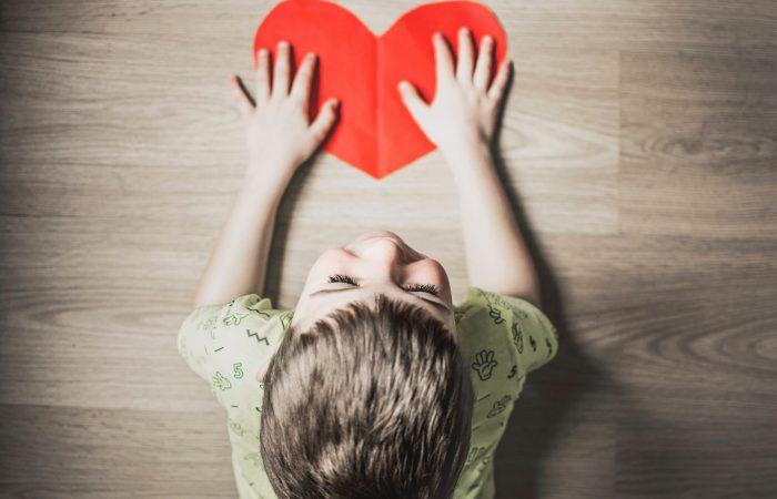 Bērns uz grīdas tur papīra sirdi | Cilmes šūnu banku alianse | LYL BioBank Hearts